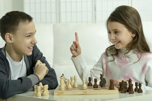 Menino e menina jogando xadrez em casa. crianças jogando xadrez