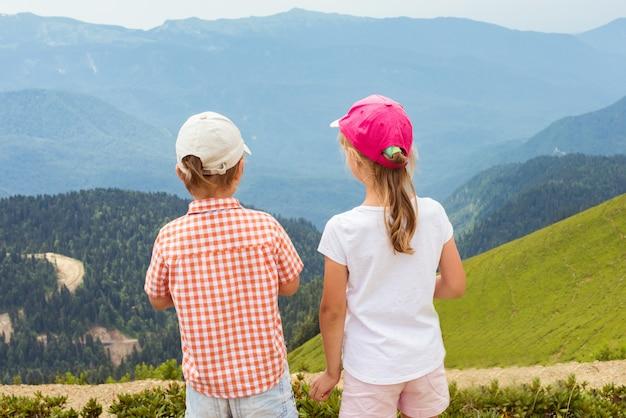 Menino e menina juntos na montanha, olhando para baixo