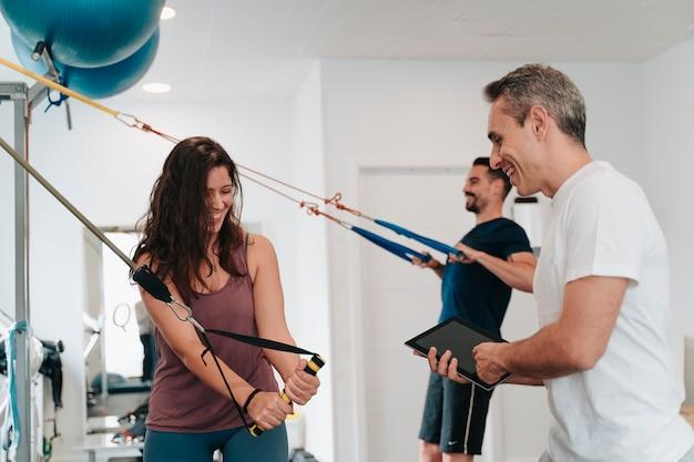 Menino e menina latinos fazendo exercícios para os braços com a ajuda de um personal trainer