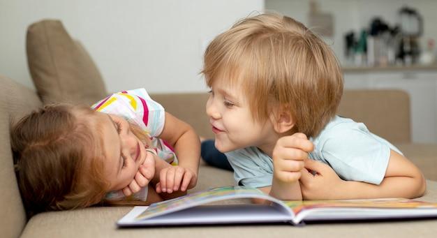 Menino e menina lendo em casa