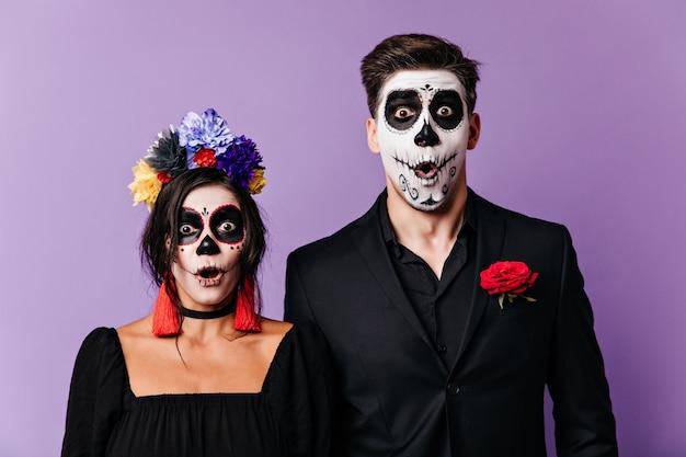 Menino e menina mexicanos de olhos castanhos abriram a boca em choque e olharam para a câmera com espanto. instantâneo de casal em imagens de carnaval posando em fundo isolado.