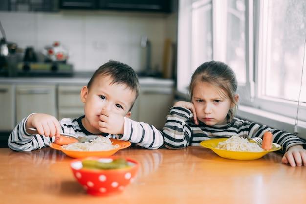Menino e menina na cozinha comendo macarrão, a menina não quer