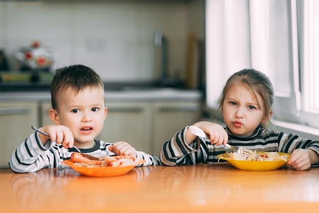 Menino e menina na cozinha comendo macarrão com muita fome