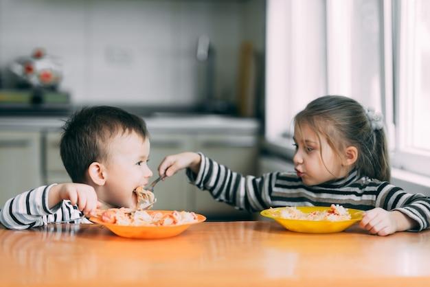 Menino e menina na cozinha comendo macarrão