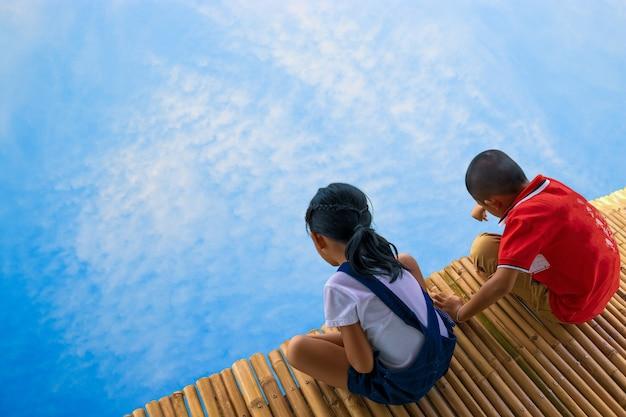 Menino e menina no conceito de bambu da ponte e do céu, da descoberta e da aventura.