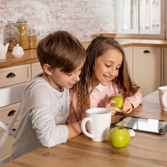 Menino e menina olhando juntos em um tablet