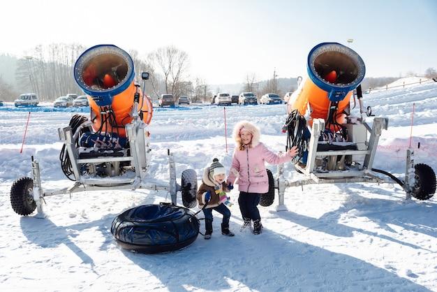 Menino e menina pulando perto do canhão de neve e tubos