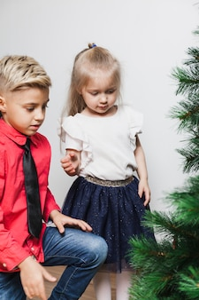 Menino e menina que decoram a árvore de natal