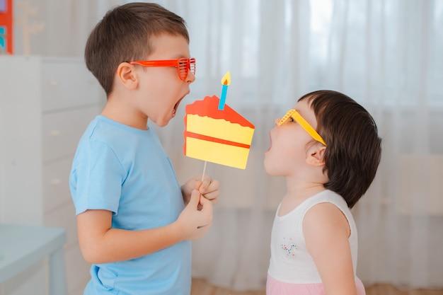 Menino e menina que jogam com o bolo de papel dos suportes com uma vela.