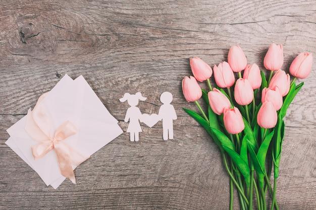Menino e menina recortados em papel e no meio há um coração em um fundo de madeira. dia dos namorados