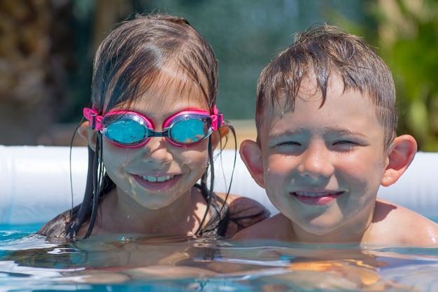 Menino e menina se divertindo na piscina.