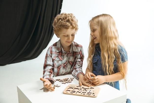 Menino e menina se preparando para a escola depois de uma longa pausa de verão. de volta à escola. pequenos modelos caucasianos brincando juntos em um espaço branco e preto