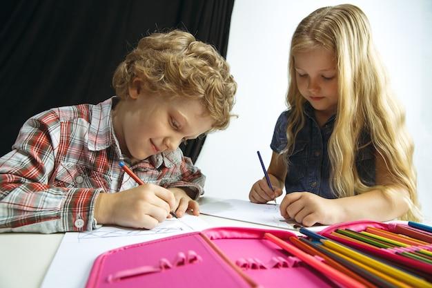 Menino e menina se preparando para a escola depois de uma longa pausa de verão. de volta à escola. pequenos modelos caucasianos desenhando juntos em fundo branco e preto. conceito de infância, educação, férias ou lição de casa.