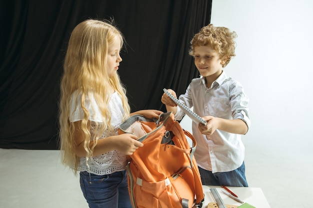 Menino e menina se preparando para a escola depois de uma longa pausa de verão