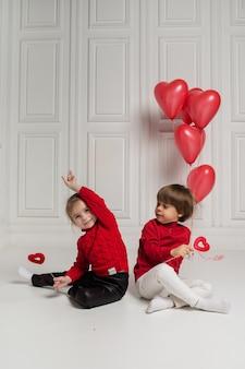 Menino e menina segurando corações vermelhos em fundo branco