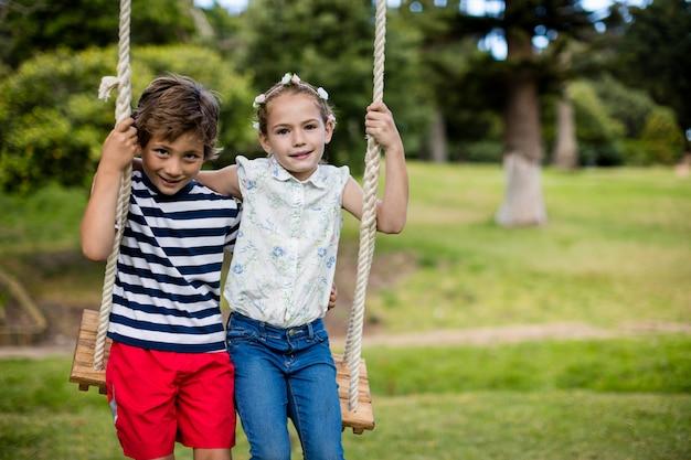 Menino e menina sentada em um balanço no parque