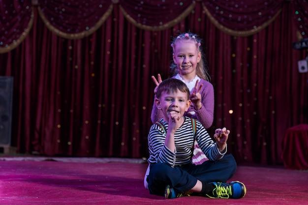 Menino e menina sentados juntos no palco, menina fazendo orelhas de coelho ou sinais de paz atrás da cabeça de meninos