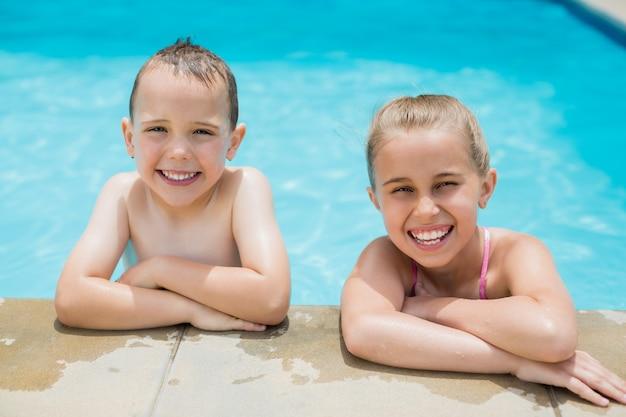Menino e menina sorrindo relaxando na beira da piscina