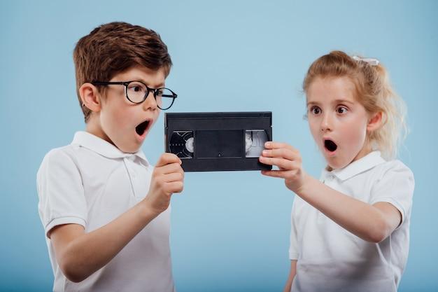 Menino e menina surpresos com uma fita de vídeo isolada em um fundo azul de aparelhos antigos