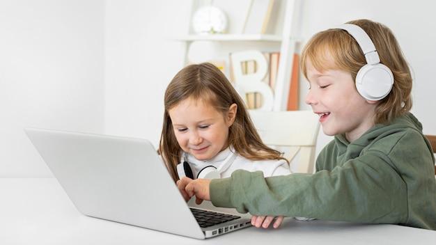 Menino e menina usando laptop com fones de ouvido