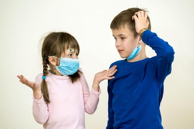 Menino e menina vestindo azul máscara médica protetora doente com vírus da varicela, sarampo ou rubéola com erupções no corpo. proteção infantil durante epidemia de coronovírus. conceito de contágio covid-19.
