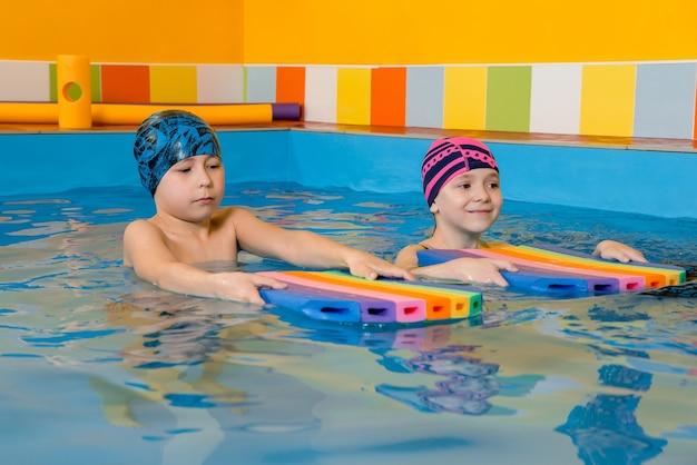 Menino e menina vestindo maiô usam uma almofada de espuma para praticar natação na piscina