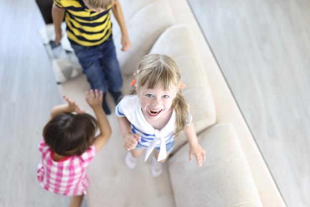 Menino e meninas riem e pulam no sofá em casa.