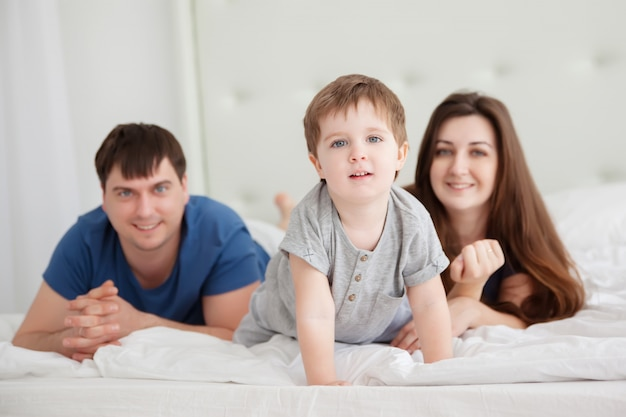 Menino e os pais na cama dos pais de pijama