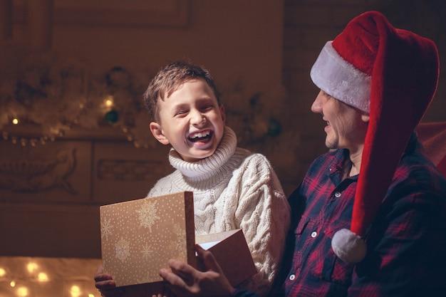 Menino e pai abrindo um presente