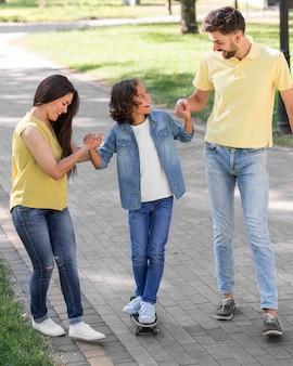 Menino e pais caminhando juntos no parque