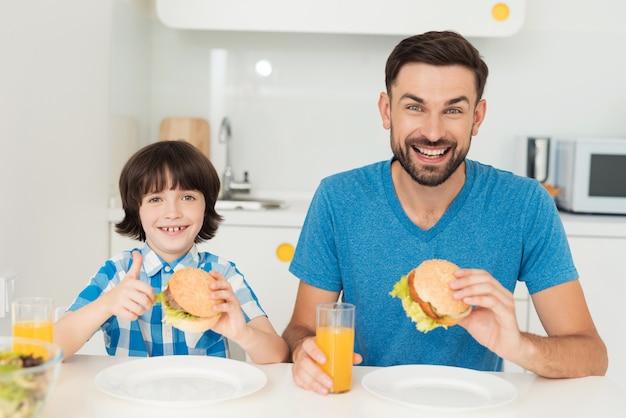 Menino e papai comem hambúrgueres na cozinha brilhante