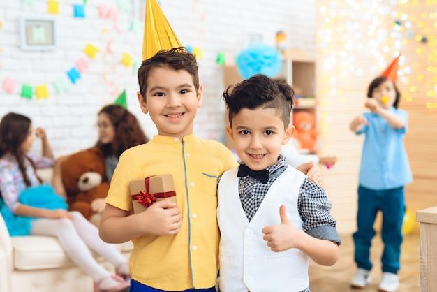 Menino e pequeno convidado com presente na festa de aniversário