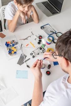 Menino e professor se divertindo construindo carros-robôs juntos na oficina