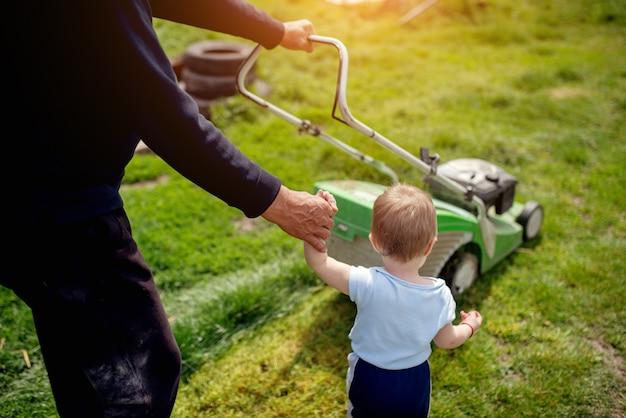 Menino e seu pai cortando a grama com cortador de grama.