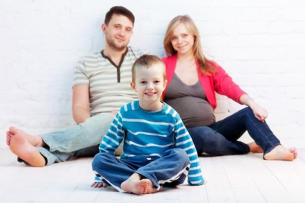 Menino e seus pais sentados no chão