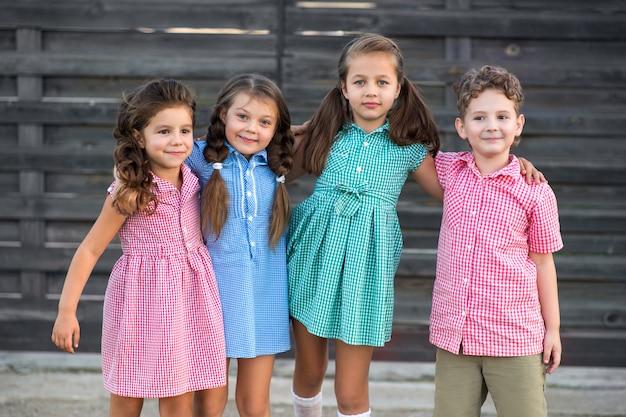 Menino e três meninas em roupas com uma foto em uma gaiola descansam na rua