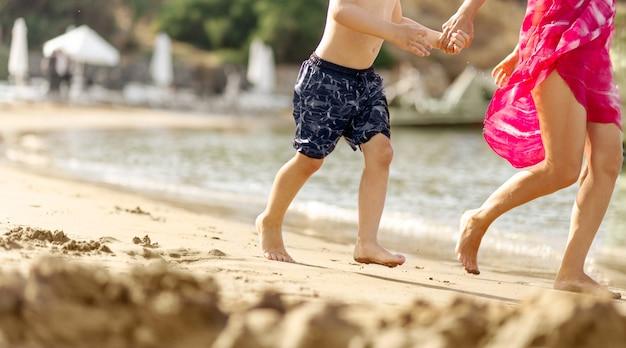 Menino e uma jovem juntos, correndo ao lado da praia de areia do mar de mãos dadas, fundo desfocado, conceito de viagem, espaço de cópia