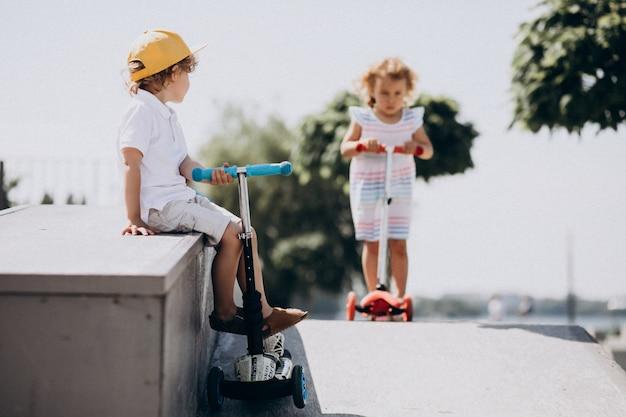 Menino e uma menina andando de scooter juntos no parque