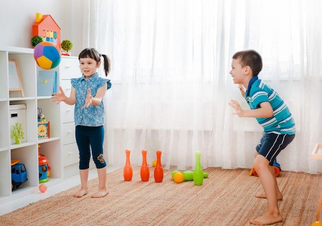 Menino e uma menina brincando com uma bola na sala de jogos para crianças