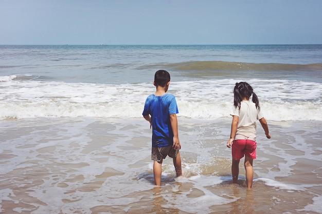 Menino e uma menina brincando na praia