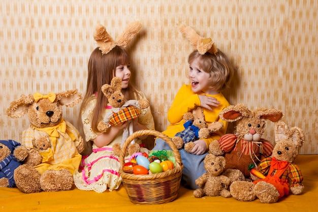 Menino e uma menina com orelhas de lebre e brinquedos