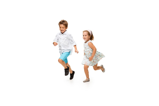 Menino e uma menina correndo em um fundo branco, feliz