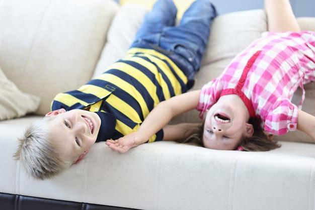 Menino e uma menina deitam-se de cabeça para baixo no sofá e riem.