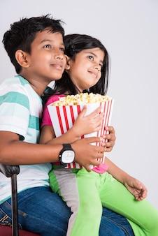 Menino e uma menina ou irmãos indianos felizes e fofinhos comendo pipoca e assistindo televisão enquanto estão sentados na cadeira