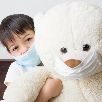 Menino e urso de pelúcia com máscara