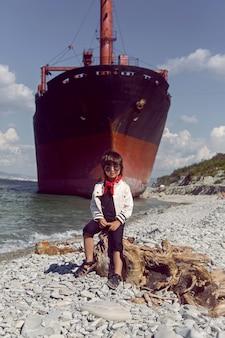 Menino elegante com cabelo comprido sentado em um tronco ao lado de um grande navio que encalhou perto de novorossiysk