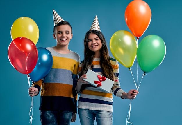 Menino elegante e linda garota com balões e uma caixa de presente, com cones de chapéus de férias em suas cabeças isoladas em um azul.