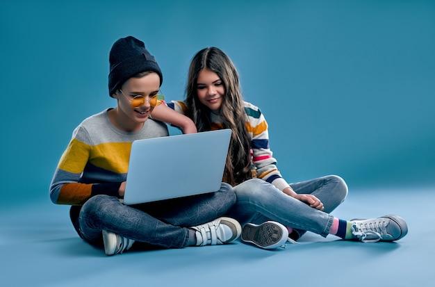 Menino elegante hipster em um chapéu e óculos e uma linda garota sentar-se de pernas cruzadas e estudar ou jogar em um laptop isolado em um azul.