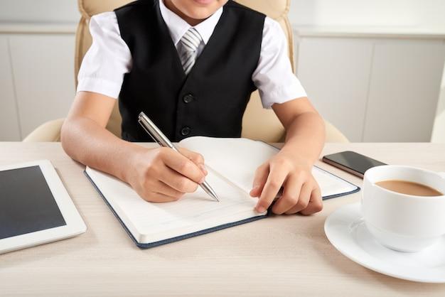 Menino elegantemente vestido irreconhecível, sentado na mesa no escritório e escrevendo no diário