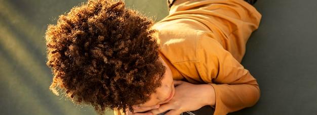 Menino em ângulo alto deitado em um campo de basquete
